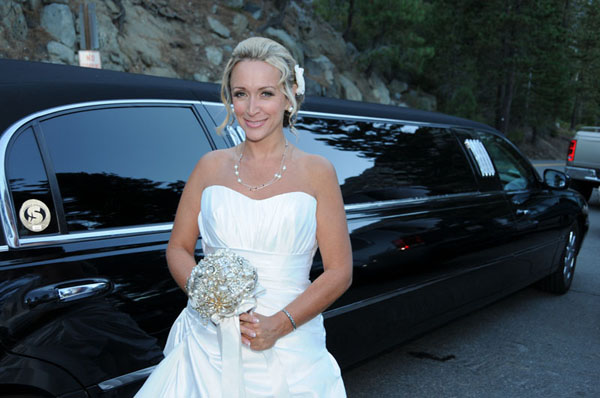 Bride poses beside the limo