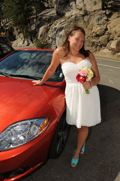 Posing by the car with her bouquet