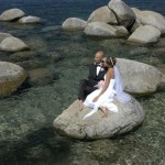 Newlyweds reflecting while sitting on a rock in the water