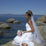 Happy bride sitting on rock
