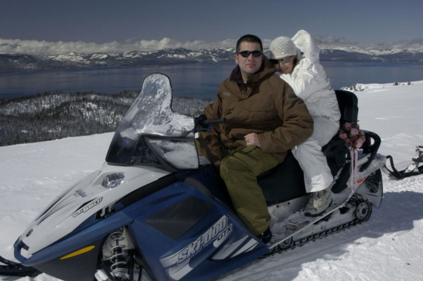 Pausing their snowmobile for a moment for a photo