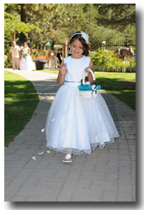 Flower girl throws petals as she walks down the wedding aisle