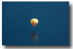 The balloon drifts serenely across the lake