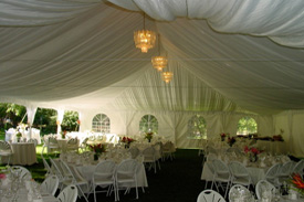 View of the inside of the tent that's setup for a reception