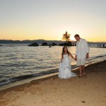 Newlyweds casually stroll the shoreline while holding hands