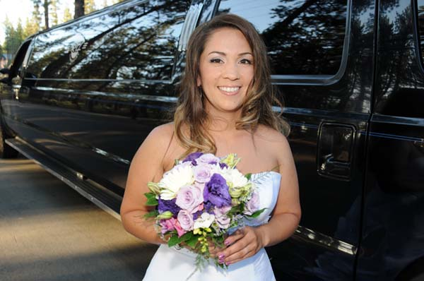 Bride poses next to the parked limo