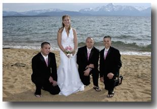 Bride standing on the beach while the groomsmen kneel