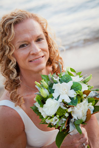 Bride smiles while holding up her bouquet