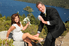 The groom displays the bride's garter while on the bluff of Emerald Bay
