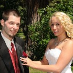 Pinning the boutonniere on her groom