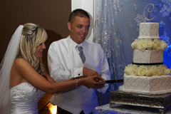 The bride and groom cutting their wedding cake at the reception