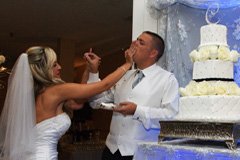 The bride smashes the wedding cake into the face of the groom