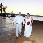 The newly married take a casual walk along the shore