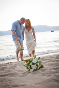 Couple dipping their toes in the sand by the waterside